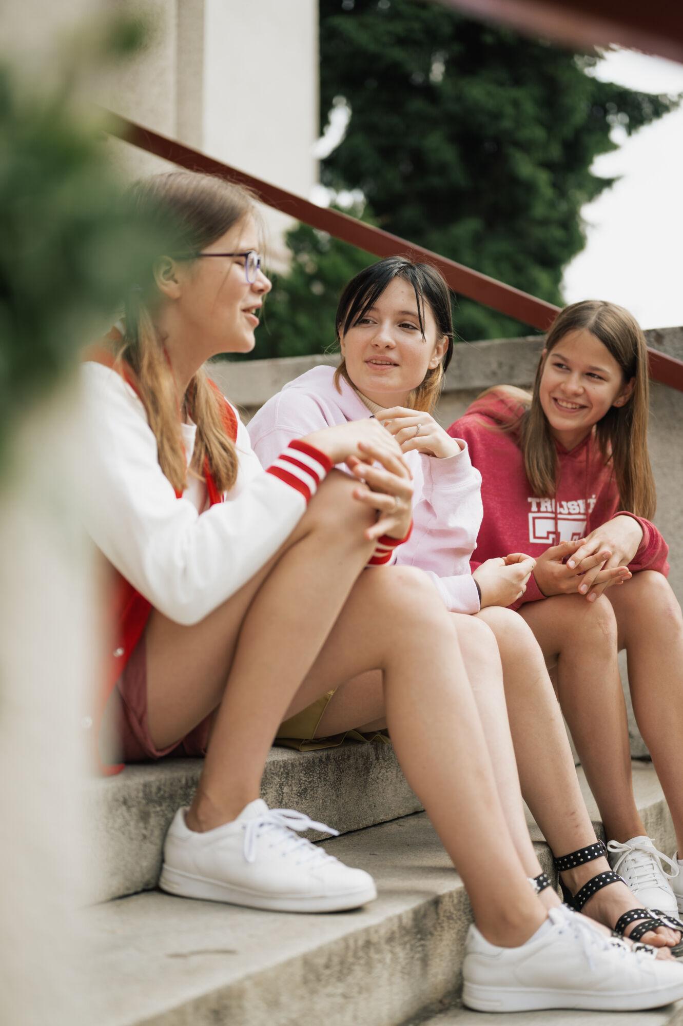 studenti TG sedící naschodech před hlavním vstupem dobudovy školy, komunikace, smích, zábava