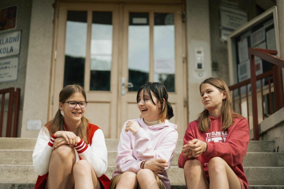 studenti TG sedící na schodech před hlavním vstupem do budovy školy, komunikace, smích, zábava
