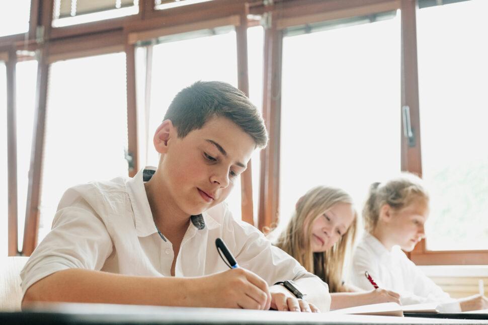 studenti Trojského gymnázia ve třídě, vyučovací hodina, studenti píšící si poznámky